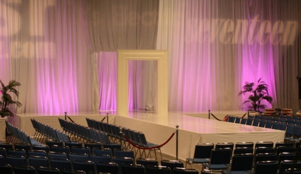 fashion show runway with uplit drapes